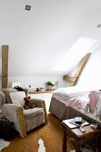 Comfortable armchair next to bed in attic room