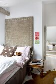 Antique bedside table next to bed against tall headboard panel upholstered in pale grey