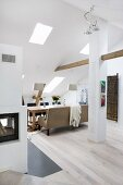 Converted, open-plan attic with pale wooden floor, dining area with table and upholstered bench