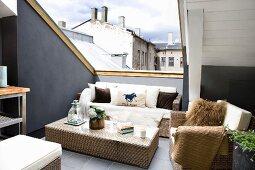 Wicker furniture in lounge area on roof terrace