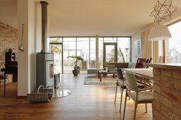 Essplatz und Loungeecke in offenem Wohnraum und freistehender Kamin vor Raumteiler