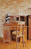 Biedermeier Stuhl vor antikem Sekretär an freigelegter Ziegelwand