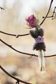 Rose in Reagenzglas mit Deko geschmückt an einem Zweig aufgehängt