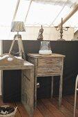 Vintage Beistelltische aus Holz vor Brüstungswand, darauf Figur und Kerzenhalter