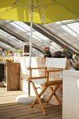 Regiestuhl unter gelbem Sonnenschirm vor Brüstungswand