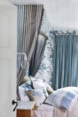 Half-tester bed with many scatter cushions and blue and grey striped canopy against floral wallpaper in romantic bedroom in shades of blue