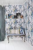 Delicate metal bench with seat cushion and scatter cushion in corner of romantic room with blue floral wallpaper