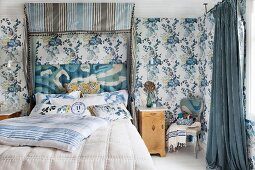 Half-tester double bed with upholstered headboard and blue and grey striped canopy in bedroom with blue floral wallpaper