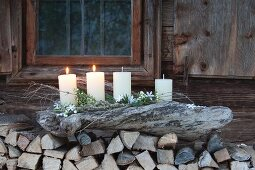 Rustikaler Adventskranz in einem groben Stück Treibholz auf einem Stapel Brennholz