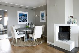 Elegant dining room in pale grey with open fireplace and dining set