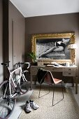 Racing bicycle next to desk below gilt-framed black and white photos
