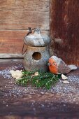 Hand-crafted felt robin next to nesting box