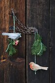 Hand-crafted felt bird pendant and sprigs of fir hanging from chain latch on vintage door