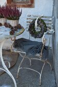Grey blanket on vintage garden chair with peeling paint and wreath of pine cones on backrest