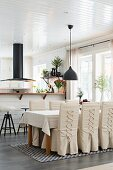 Chairs with loose, laced covers in dining area in open-plan kitchen with black extractor hood above counter
