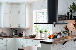 White kitchen with wooden worksurface, extractor hood and breakfast bar