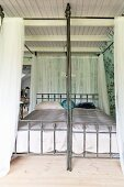 Vintage four-poster bed with airy curtains on metal frame