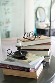 Candlesticks and reading glasses on stacked books