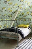 Grey-painted vintage bed under sloping ceiling with vintage-style floral wallpaper