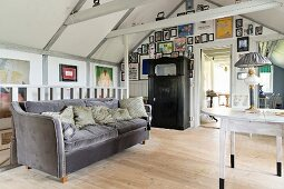Grey velvet sofa, round table, vintage oil lamp and collection of pictures on gable-end wall