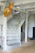 Old ship's figurehead hung on wooden structure in front of winding wooden staircase painted pale grey in rustic interior