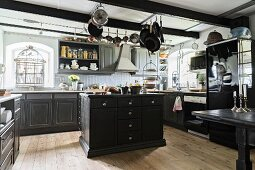 Spacious kitchen with black-painted, traditional-style base units and island counter below cooking utensils hung from ceiling