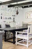 White-painted armchairs around table with carved base frame in rustic dining room with mural on wall