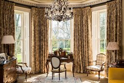 Classic desk and Baroque chairs in window bay with lattice windows and opulent curtains