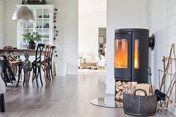 Cast iron log burner with firewood compartment and dining area in open-plan interior with white wood cladding