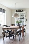 Wooden chairs around dining table with peeling paint below metal pendant lamp in dining area with white, wood-clad walls
