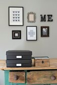 Black storage boxes with labels and wooden box on table below framed pictures on grey wall
