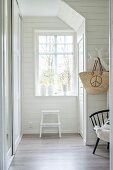 White, wood-panelled hallway with step ladder below window