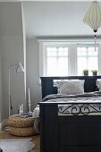 Antique, black-painted wooden bed and standard lamp with stainless steel lampshade below window in bedroom painted pale grey