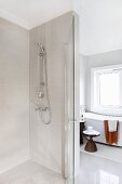Floor-level shower with glass door, side table in background next to bathtub below window in modern bathroom with vintage ambiance