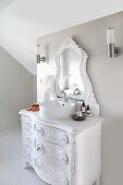 Vintage chest of drawers with modern countertop sink and carved vanity mirror painted white in modern, attic bathroom painted pale grey