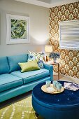 Cups on tray on blue, velvet, round ottoman and pale blue sofa in living room; ornately patterned wallpaper on accent wall