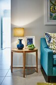 Bowl of fruit and table lamp on round, wooden side table next to pale blue couch