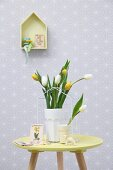 Pastel Easter arrangement; vase of tulips and lamb ornament on small table