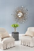 Elegant armchairs with valances on white-painted wooden floor and sunburst mirror on blue wall