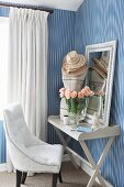 Easy chair next to tailors' dummy, mirror and vase of roses on vintage tray table against elegant striped wallpaper