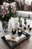 Small gift and tealight holders on stacked books on tray in front of glass vase of roses on coffee table