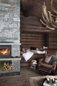 Cosy living area with brown leather armchair in front of alcove in log wall and fire in fireplace