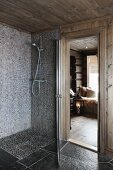 Floor-level shower with mosaic tiles next to open door with view of floor lantern in living area