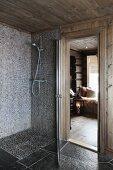 Floor-level shower with mosaic tiles next to open door with view of floor lantern in living area