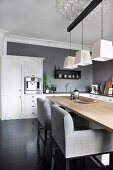 Upholstered chairs with pale grey covers at wooden table below three pendant lamps in kitchen-dining room