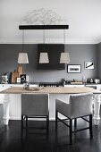 Chairs with pale grey upholstery around wooden table below modern pendant lamps in elegant kitchen