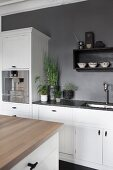 Island counter with wooden worksurface opposite kitchen counter with white base units against grey-painted wall
