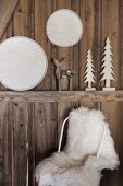 Chair with white sheepskin below Christmas decorations on rustic wooden wall
