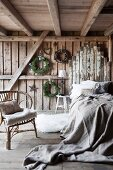 Bedroom in rustic wooden house with cane chair next to bed with linen bedspread and headboard made from reclaimed boards