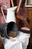 Retro Emaillekanne, Metalleimer und Besen auf antikem Armlehnstuhl